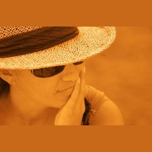 se protéger du soleil avec un  chapeau et des lunettes